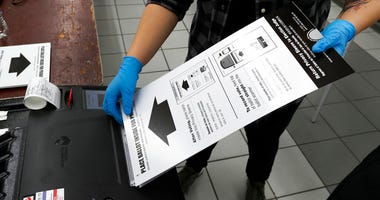 In this March 17, 2020, file photo a poll worker at the Su Nueva Lavanderia polling place uses rubber gloves as she enters a ballot in the ballot box in Chicago.