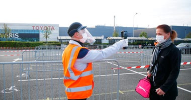 An employee has her temperature taken at the Toyota car factory in Onnaing, northern France, Monday, April 27, 2020.