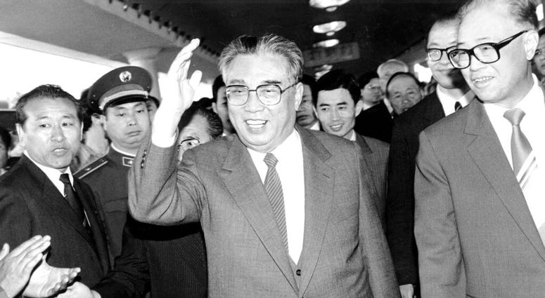 In this May 21, 1987, file photo, then North Korean President Kim Il Sung, center, and then Chinese Premier Zhao Ziyang make their way through a crowd of well-wishers at the train station in Beijing.