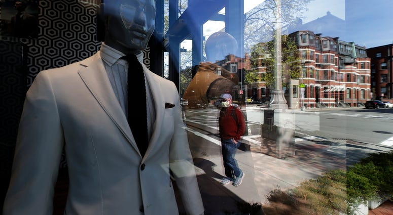 A passer-by wearing a mask out of concern for the COVID-19 coronavirus, background center, walks past mannequins in a clothing store, Wednesday, April 29, 2020, in Boston.