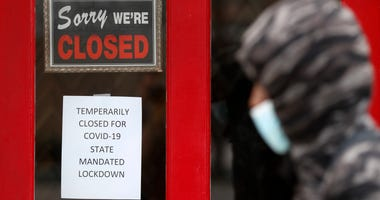A pedestrian walks by The Framing Gallery, closed due to the COVID-19 pandemic, in Grosse Pointe, Mich., Thursday, May 7, 2020.