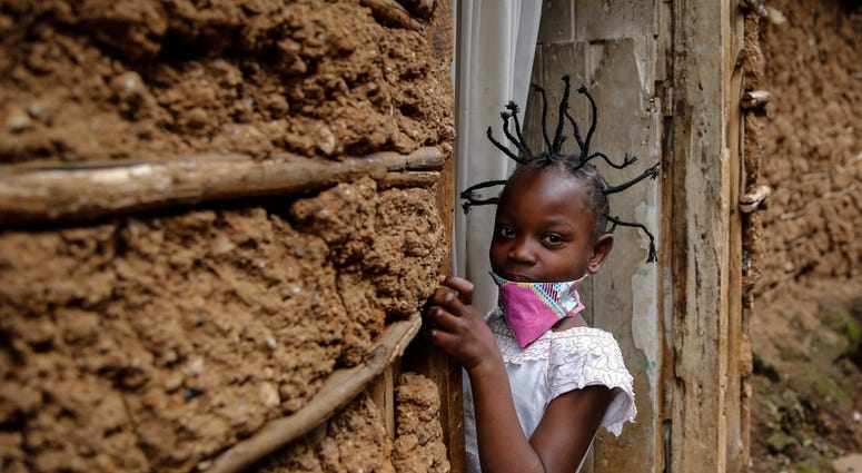 Jane Mbone, 7, arrives home after having her hair styled in the shape of the new coronavirus at the Mama Brayo Beauty Salon in Nairobi, Kenya, Sunday, May 3, 2020.