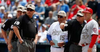 Kansas City Royals bench coach Chino Cadahia (15) and St. Louis Cardinals first base coach Chris Maloney (37) exchange line-ups with home plate umpire Rob Drake (30) before a baseball game at Kauffman Stadium in Kansas City, Mo., May 27, 2013.