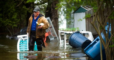 Mark Musselman brings a chair to the front of his house from the back yard, wading through floodwater, Tuesday, May 19, 2020 in Edenville, Mich.