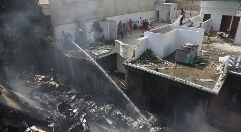 Fire brigade staff try to put out fire caused by plane crash in Karachi, Pakistan, Friday, May 22, 2020.