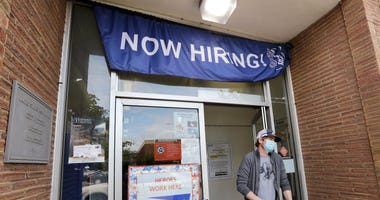 this June 4, 2020, file photo, a customer walks out of a U.S. Post Office branch and under a banner advertising a job opening, in Seattle.