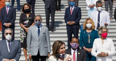 House Speaker Nancy Pelosi of Calif., joined by House Democrats spaced for social distancing, speaks during a news conference on the House East Front Steps on Capitol Hill in Washington, Thursday, June 25, 2020.