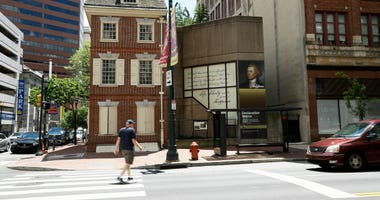 In this June 30, 2020, photo, a man walks in front of the Declaration House in Philadelphia.