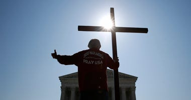 Tom Alexander holds a cross as he prays prior to rulings outside the Supreme Court on Capitol Hill in Washington, Wednesday, July 8, 2020.