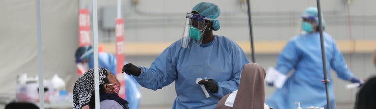 In this Monday, July 6, 2020 file photo, a health care worker administers a COVID-19 test at a site sponsored by Community Heath of South Florida at the Martin Luther King Jr. Clinica Campesina Health Center in Homestead, Fla.