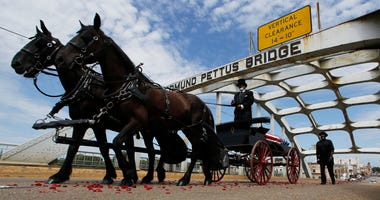 The casket of Rep. John Lewis moves over the Edmund Pettus Bridge by horse drawn carriage during a memorial service for Lewis, Sunday, July 26, 2020, in Selma, Ala.