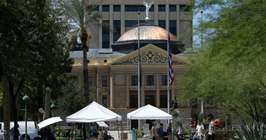 As flags fly at half-staff at the Arizona Capitol in memory of the late Arizona Republican Sen. John McCain, television crews broadcast live Sunday, Aug. 26, 2018, in Phoenix.