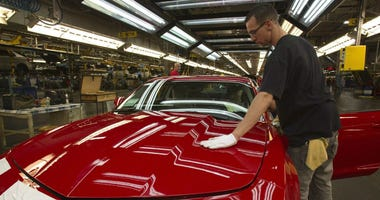 In this June 10, 2011, file photo, a worker checks the paint on a Camaro at the GM factory in Oshawa, Ontario.