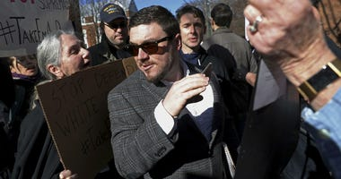 In this Feb. 27, 2018, file photo, Jason Kessler walks through a crowd of protesters in front of the Charlottesville Circuit Courthouse ahead of a decision regarding the covered Confederate statues, during a rally in Charlottesville, Va.