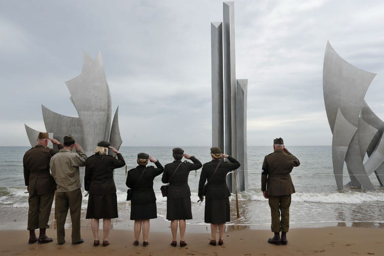 Enthusiasts of England salute in front of The Brave, a monument dedicated to the American soldiers who landed on Omaha Beach on D-Day, in Saint-Laurent-sur-Mer, Tuesday, June 4, 2019, in Normandy.