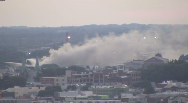 Smoke still pours from the scene of a huge junk yard fire in Kensington, Philadelphia.