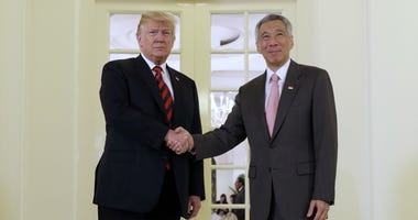 President Donald Trump shakes hands as he meets with Singapore Prime Minister Lee Hsien Loong
