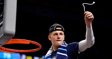 Villanova Wildcats guard Donte DiVincenzo cuts down the net after beating the Michigan Wolverines in the championship game of the 2018 men's Final Four at Alamodome.