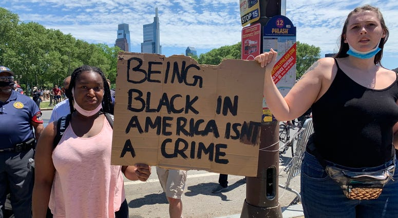 A pair of demonstrators holding a sign at the Philadelphia Museum or Art Saturday afternoon. The planned protests began peacefully, but erupted into violence after marchers left the Art Museum.