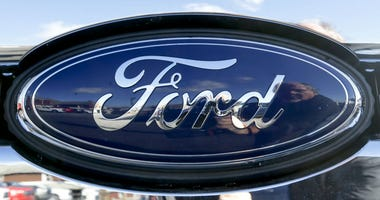 This Nov. 19, 2015 file photo shows the blue Ford oval badge in the grill of a pickup truck on the sales lot at Butler County Ford in Butler, Pa.