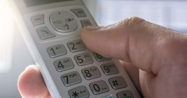 Person dials a telephone number on a touch-tone receiver.