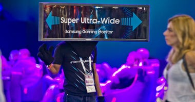 COLOGNE, GERMANY - AUGUST 21: A steward wears a super ultra wide videoscreen on his head to guide visitors to Samsung booth at 2018 gamescom fair press day on August 21, 2018 in Cologne, Germany.
