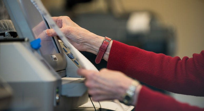 Election official Mary Wickersham enters selections into a voting machine during a public accuracy testing of Election Day voting machines, Oct. 23, 2018 in Minnesota.
