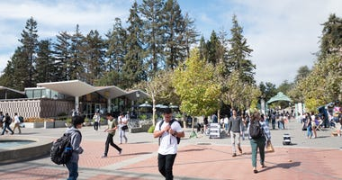 Large crowds of students walk through the campus of UC Berkeley
