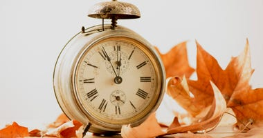 Closeup of an alarm clock surrounded by dry leaves, depicting the end of the summer time and the beginning of autumn.