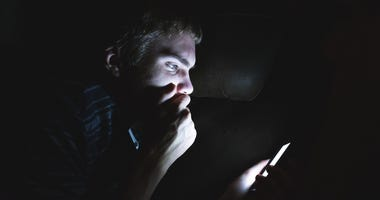 Shocked teen scrolling social media in the dark.