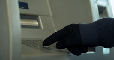 Gloved hand enters PIN to withdraw cash from an ATM.
