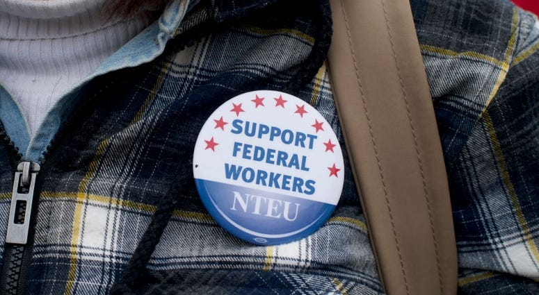 """A woman wears a National Treasury Employees Union pin stating """"SUPPORT FEDERAL WORKERS"""" while joining area elected officials and furloughed federal workers at a rally in front of Independence Hall on Jan. 8, 2019."""