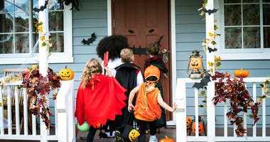 Trick-or-treaters walking up to a house.
