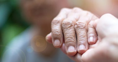 An elderly person holding a caregiver's hand