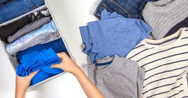 A person organizing shirts.