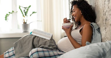 A pregnant woman eating, reading a book.
