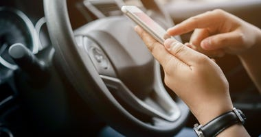 Person holding a smartphone while behind the wheel