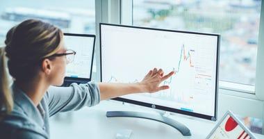 Woman looking at data on computer screens