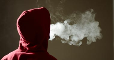Young male in red hoodie vaping smoking, exhales thick vapor.