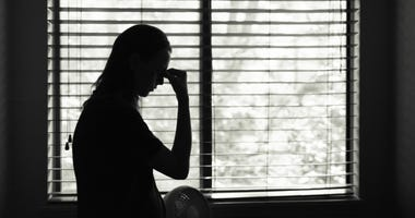 A woman in silhouette against a bedroom window