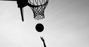 Silhouette of woman playing basketball