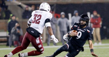 Desmond Ridder #9 of the Cincinnati Bearcats avoids a tackle from Benny Walls #32 of the Temple Owls during the second quarter at Nippert Stadium on November 23, 2019 in Cincinnati, Ohio.
