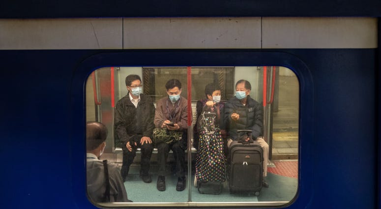 Passengers wearing protective masks wait on a train ahead of departure at the Lo Wu MTR station, where one of the border checkpoints government announced to be shutdown, on February 3, 2020 in Hong Kong, China.