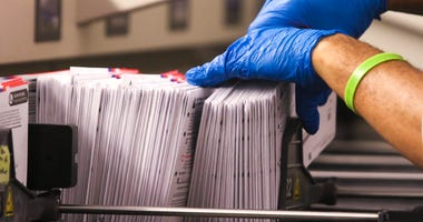 An election worker handles vote-by-mail ballots.