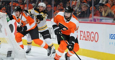 Nate Thompson #44 of the Philadelphia Flyers skates with the puck as Nicolas Aube-Kubel #62 gets checked by Matt Grzelcyk #48 of the Boston Bruins in the third period at Wells Fargo Center on March 10, 2020 in Philadelphia, Pennsylvania. The Bruins won 2-
