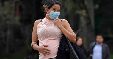 A pregnant woman wears a face mask as a preventive measure against the spread of the new coronavirus, COVID-19.