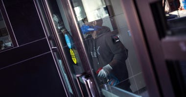 A worker disinfects the front doors of a school.