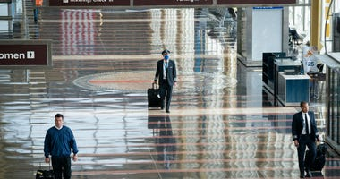 A pilot wears a face covering as he walks through a mostly empty terminal at Ronald Reagan Washington National Airport.