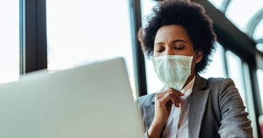African American businesswoman with protective mask working on laptop in the office