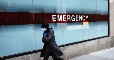 A woman walks by the emergency entrance to Mount Sinai Hospital amid the coronavirus pandemic on March 31, 2020, in New York City.